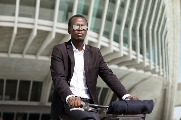 Успешный, экологически сознательный молодой афроамериканский предприниматель, предпочитающий велосипед, чтобы добраться до офиса, вместо того, чтобы выбирать транспорт или автомобиль, который загрязняет воздух, заботясь об окружающей среде