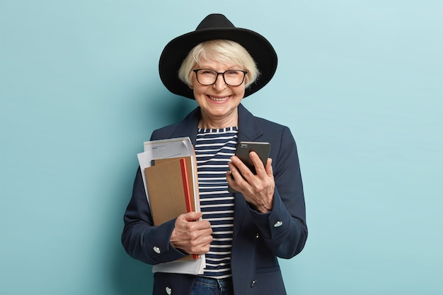Successful elderly smiling businesswoman checks data information on mobile phone, holds notepad with documents, returns from important conference, dressed in stylish clothes, makes payment online