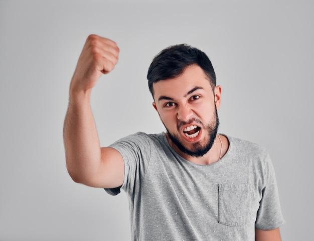 Успешный эмоциональный молодой кавказский спортсмен-мужчина с темными волосами кричит «да» и поднимает в воздух сжатые кулаки, чувствуя себя взволнованным. люди, успех, триумф, победа, победа и праздник