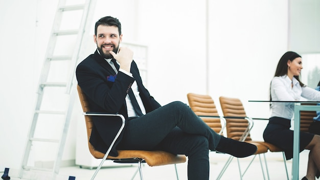 Successful employee of the company sits on a chair near the workplace in the office.