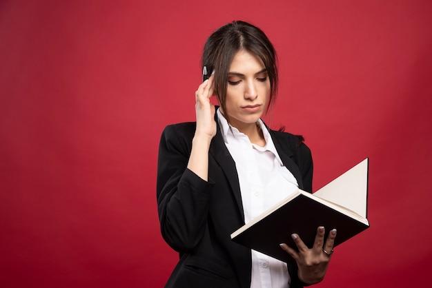 Успешный сотрудник, читающий ее книгу памяти на красном фоне.