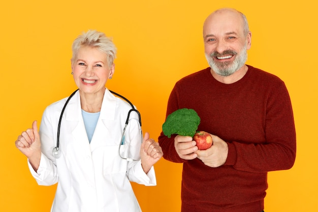 Successful energetic middle aged woman physician with stethoscope around her neck having excited facial expression, her happy senior patient choosing healthy diet, holding broccoli and apple, smiling