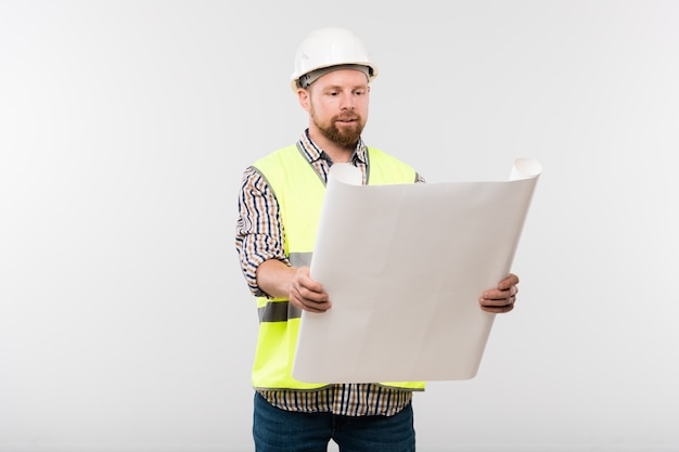 Successful engineer or foreman in protective helmet and workwear holding blueprint in front of himself while looking at sketch