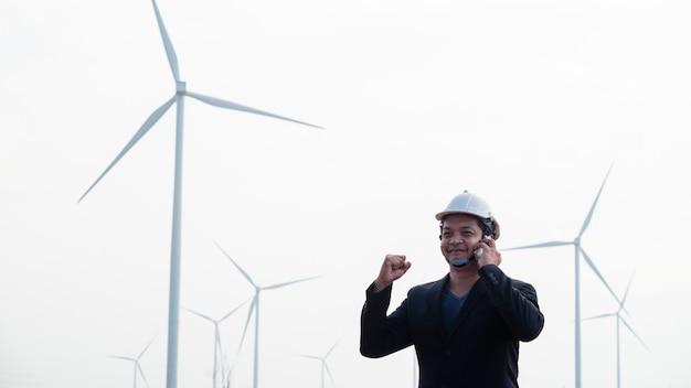 成功したエンジニアが立って、風力タービン分野でスマートフォンを使用