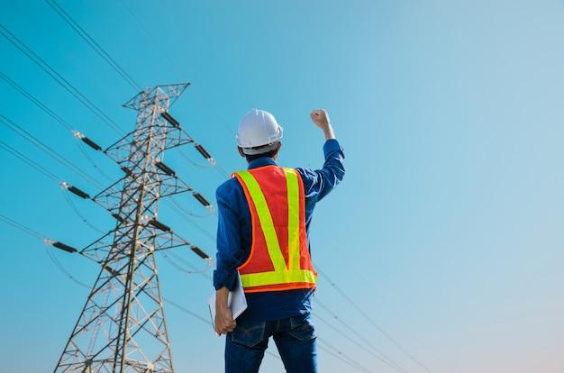 成功したエンジニアは、青い背景の高電圧ポールに立ち向かいます。