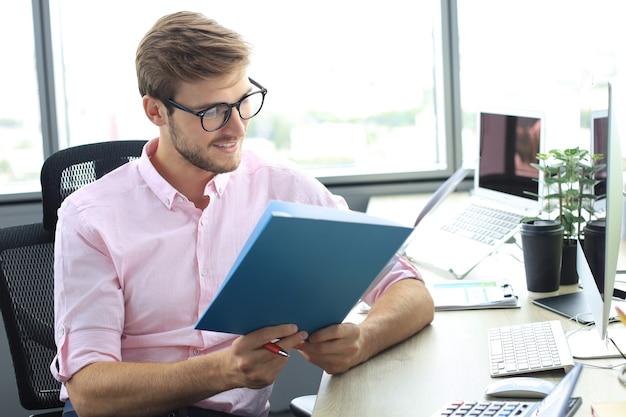 Успешный предприниматель внимательно и сосредоточенно изучает документы.
