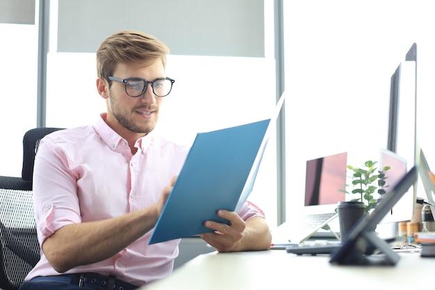 成功した起業家は、注意深く集中した見た目で文書を研究しています。