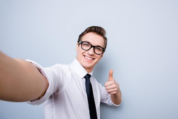 Успешный возбужденный молодой парень в очках и официальной одежде делает селфи на камеру, стоит на чистом пространстве, показывает палец вверх и улыбается