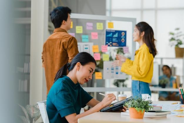 성공적인 임원 아시아 젊은 사업가 스마트 캐주얼 드로잉, 쓰기 및 현대 사무실에서 영감 검색 아이디어 작업 과정의 디지털 태블릿 컴퓨터 생각 펜을 사용하여 착용하십시오.