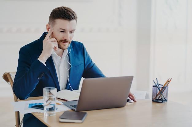 イヤホンを使用して従業員とオンライン会議を行う正式な青いスーツを着たエグゼクティブ マネージャー、オフィスの机の後ろのラップトップの前に座って話しているビジネスマンは真剣に取り組んでいます