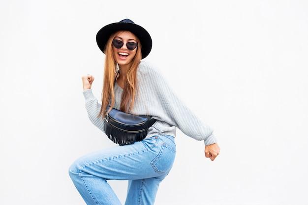 Успешная возбужденная стильная девушка с откровенной улыбкой позирует на белой городской стене
