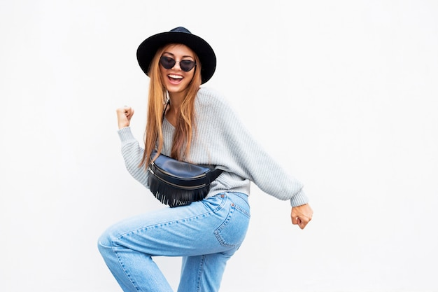 Successful  exited stylish girl with candid smile posing on white urban wall