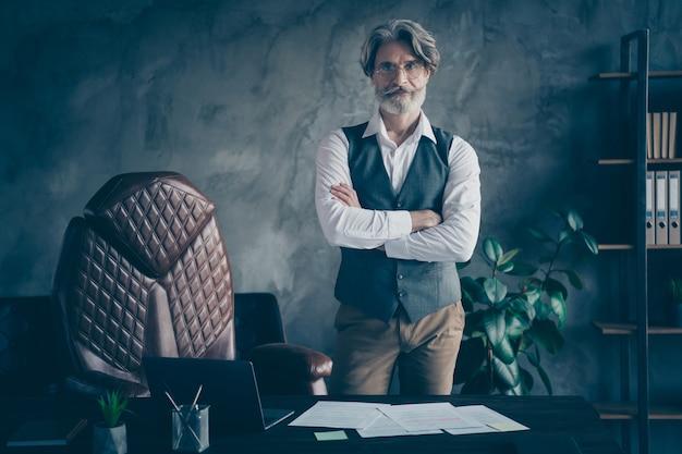 Успешный опытный бизнесмен стоит на современном чердаке со скрещенными руками