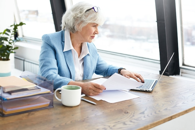 Successful experienced elderly female lawyer wearing nice suit and glasses on her head using portable computer at her workplace, looking at screen with focused concentrated facial expression