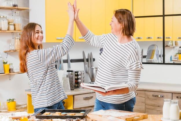 성공적인 가족 협력. 엄마와 딸은 비스킷 굽기를 끝내고 일에 만족하며 하이 파이브를하고 웃었다.