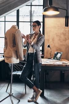 Успешный модельер. полная длина серьезной молодой женщины в очках, использующей швейные иглы для шитья куртки на манекене, стоя в своей мастерской