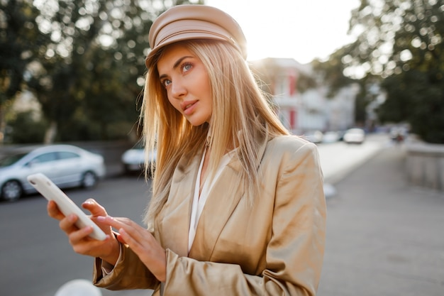 Успешная модная европейская женщина в элегантном повседневном обмундировании позирует мобильный телефон открытый. цвета заката.