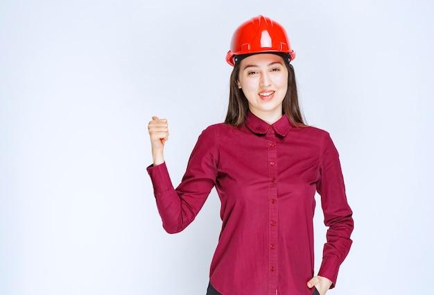 빨간색 하드 헬멧에 서서 엄지손가락을 포기하는 성공적인 여성 건축가.