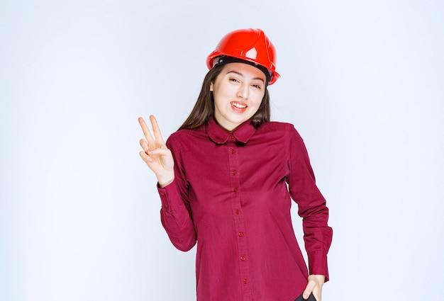 立って勝利のサインを与える赤いヘルメットで成功した女性建築家。