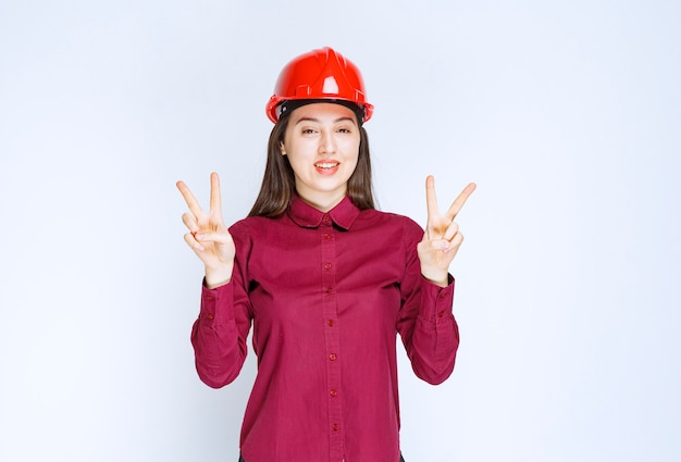 빨간색 하드 헬멧을 쓴 성공적인 여성 건축가가 서서 승리의 사인을 합니다.
