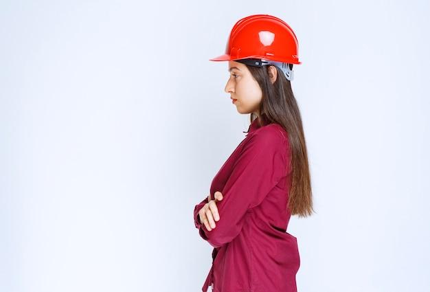赤いヘルメットをかぶって立って彼女の側を見ている成功した女性建築家。