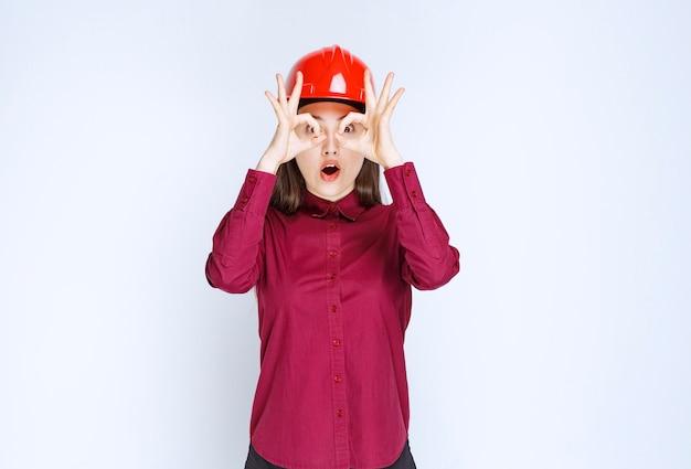 서서 포즈를 취하는 빨간 헬멧을 쓴 성공적인 여성 건축가.