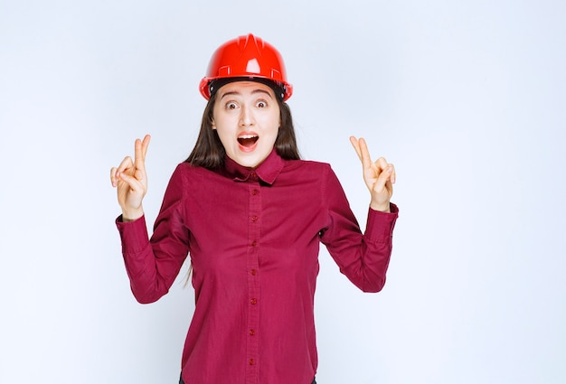 Successful female architect in red hard helmet standing and giving signs.