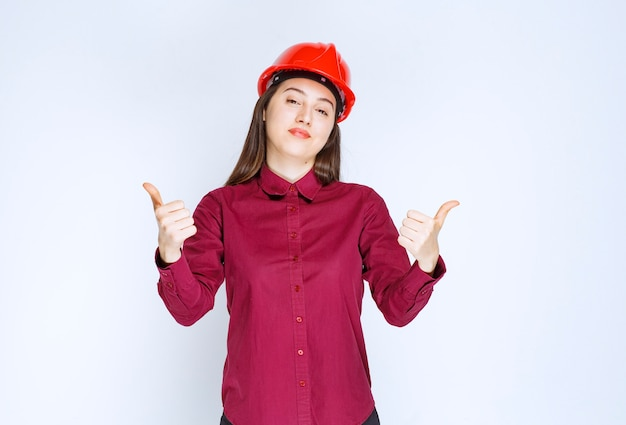 Successful female architect in red hard helmet standing and giving thumbs up.