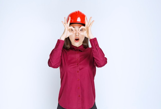 Successful female architect in red hard helmet standing and posing.