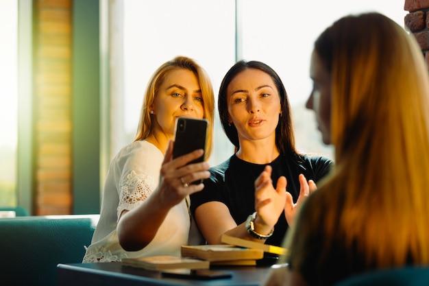 カジュアルアパレルで成功した女性ブロガーが、友好的な会議中にスマートフォンのソーシャルネットワークで公開するために自分撮り写真を作成します。学生のコーヒーブレイク。セレクティブフォーカス。