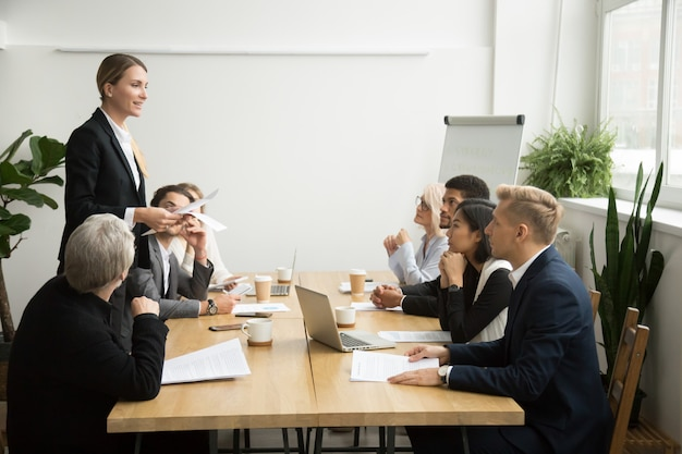 Successful female boss leading team meeting talking to multiracial employees