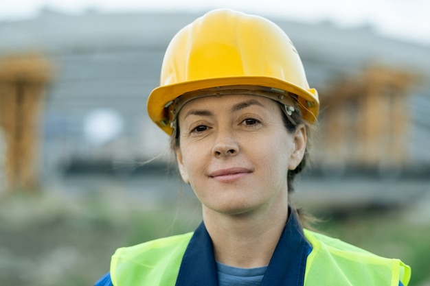 あなたを見ている保護ヘルメットで成功した女性ビルダー