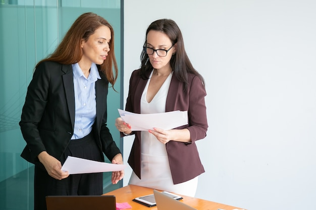 Successful female colleagues holding documents, reading report and standing in conference room together