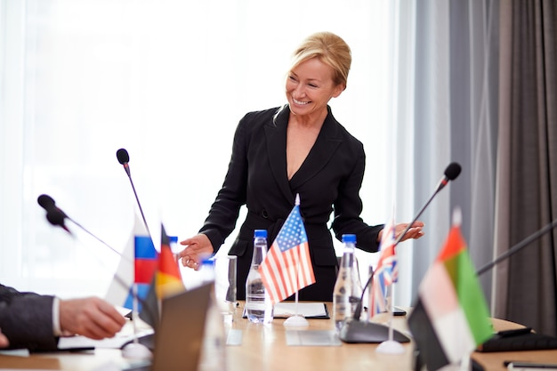 Successful female executive in formal suit giving speech with political leaders of other countries, diverse people gathered at press conference, meeting without ties