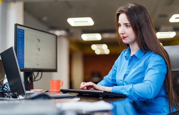 Успешная женщина-программист сидит за столом с компьютером во время работы. красивая женщина, глядя на монитор в офисе компании программного обеспечения.