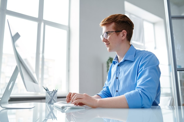 Successful financial analyst sitting by desk in front of computer screen while looking through online information