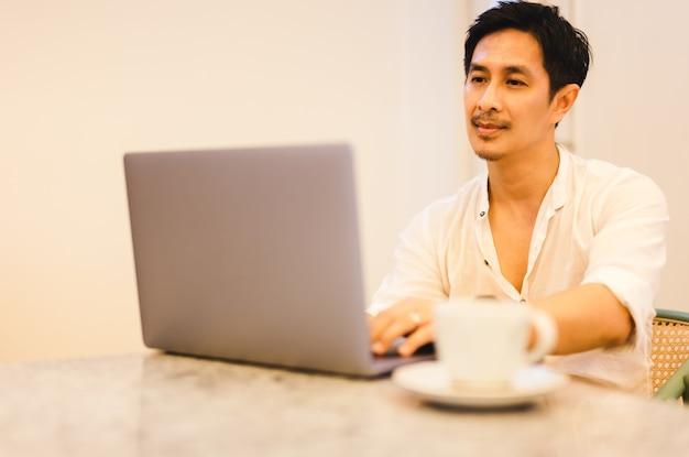 現代のキッチンに座っているコンピューターでオンラインで作業するラップトップを使用して成功したフリーランサーの男