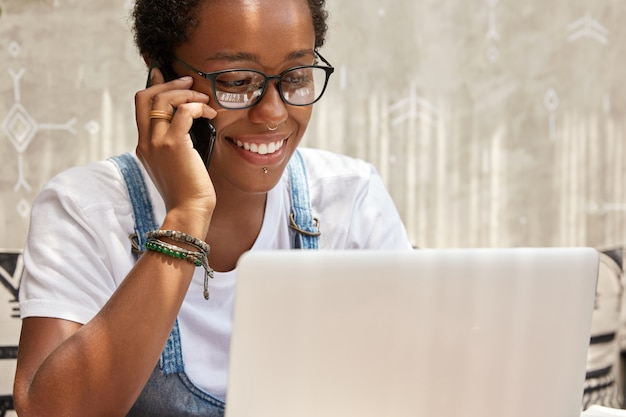 Il manager di successo della giovane donna felice chiama tramite smart phone mentre lavora sul computer portatile