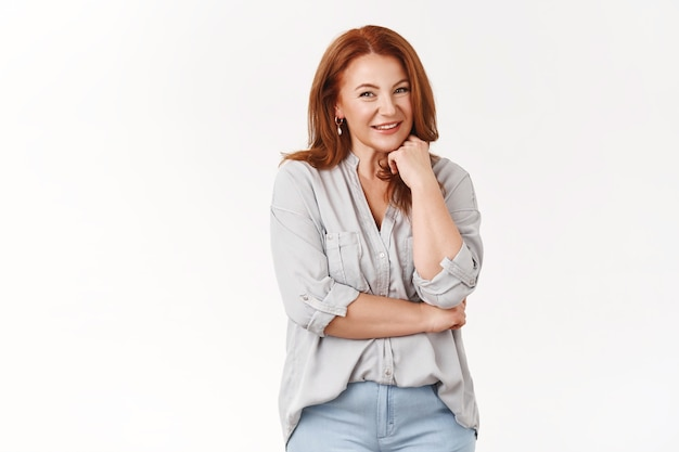 Successful gorgeous redhead middle-aged female stylish neat outfit lean fist face-line smiling amused entertained have conversation barbecue party garden look amused happy talking, white wall