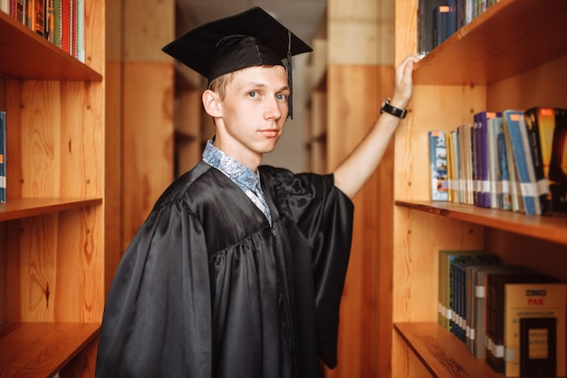 Successful graduate guy in academic outfit