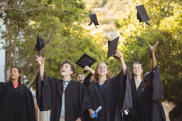 Успешные аспиранты бросают доску в воздух в кампусе
