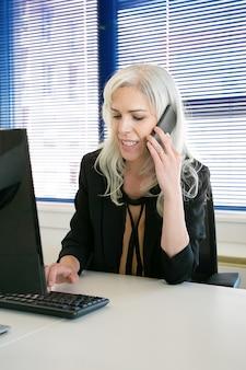성공적인 회색 머리 여성 ceo는 핸드폰으로 이야기하고 키보드에 입력합니다. 콘텐츠는 사무실 방에서 일하는 아름다운 사업가를 경험했습니다. 비즈니스, 회사 및 생산성 개념