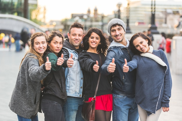 Successful group of friends showing thumbs up