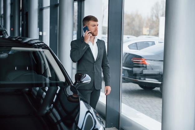 Ragazzo di successo. uomo d'affari barbuto elegante moderno nel salone dell'automobile