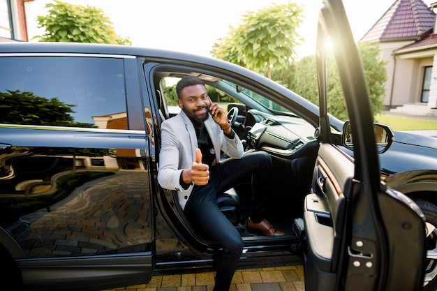 Successful handsome african man businessman and boss sitting in the car, talking on the phone, smiling, and showing thumb up. business concept