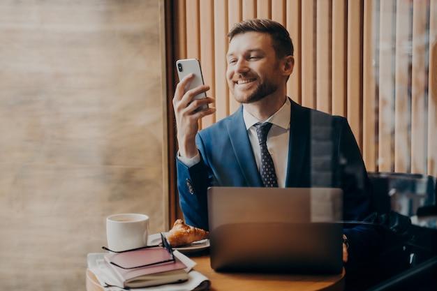 파란색 정장을 입은 성공적인 미남 사업가는 노트북이 있는 아늑한 카페에 앉아 원격으로 작업하고 문서와 크루아상을 식탁에 올려놓고 스마트폰으로 좋은 소식을 확인하고 웃고 있습니다.