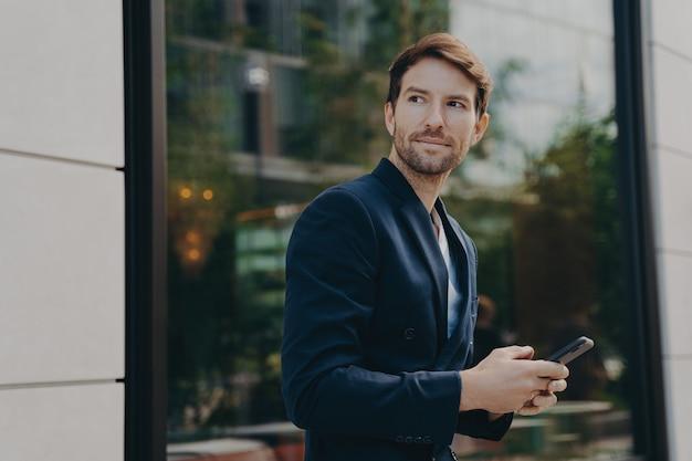 Успешный красивый бизнесмен обменивается сообщениями с клиентом на смартфоне, стоя рядом со зданием