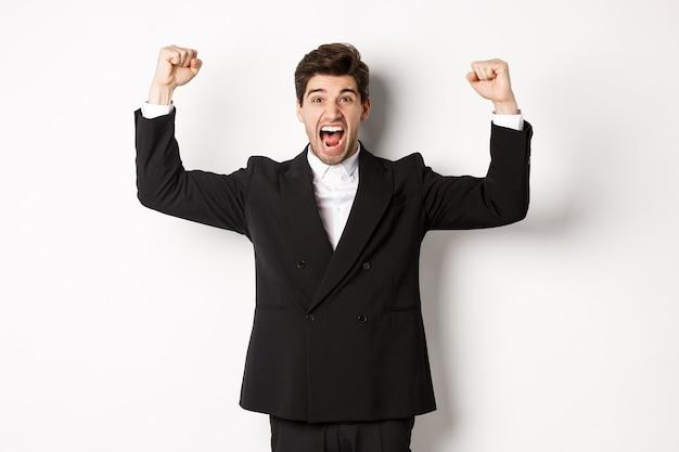 Un bell'uomo d'affari di successo che trionfa, alza le mani e grida sì, rallegrandosi per il successo, in piedi su sfondo bianco.