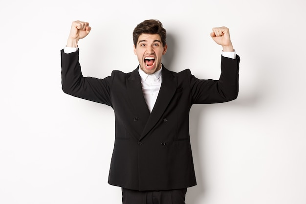 Successful handsome businessman triumphing, raising hands up and shouting yes
