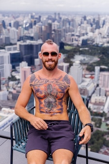 成功したハンサムなヨーロッパのひげを生やした残忍な入れ墨の強い男は、時計でトップレスが素晴らしい街の景色を望む高層階の椅子に座っています